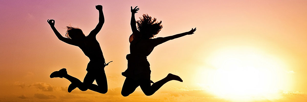 silhouette of girls jumping in a sunrise